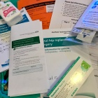A pile of papers and booklets from the hospital with information on hip replacements, exercises, MRSA and MSSA